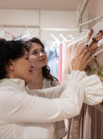 Young woman with shop assistant choosing evening dress